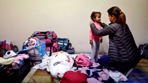 A woman dresses a girl while staying at a shelter with fellow members of a caravan of migrants from Central America, prior to preparations for an asylum request in the U.S., in Tijuana